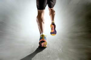 close up view strong athletic legs with ripped calf muscle of young sport man running isolated on motion grunge background in sport fitness endurance and high performance concept