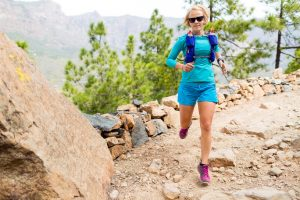 Trail runner woman cross country running in mountains inspirational landscape. Training and working out runner jogging and enjoy outdoors in nature rocky footpath on Canary Islands Spain