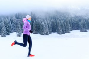 Sport fitness inspiration and motivation. Young happy woman cross country running in mountains on snow winter day. Female trail runner jogging exercising outdoors.